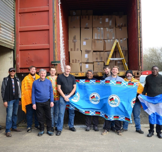Team in front of nearly full container on shipping day
